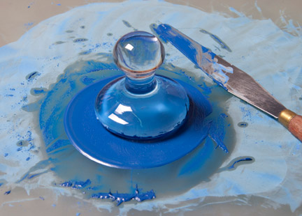 Blue pigment being ground with oil to make a paint