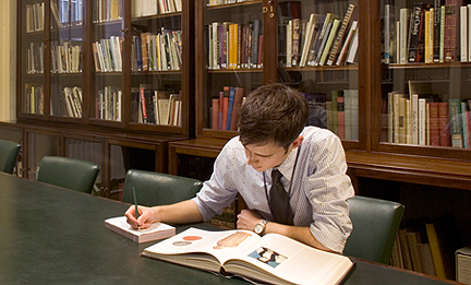A man using a book at a table in the gallery library