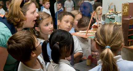 A teacher and children looking at an exhibit in a glass case