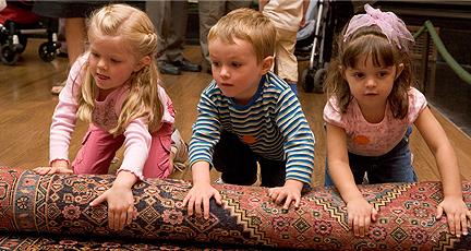 Three children rolling up a workshop carpet