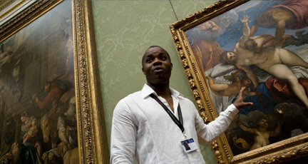 A tour guide explains a painting