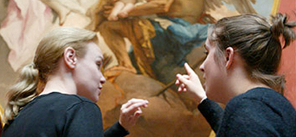 Two women having an animated discussion about a painting